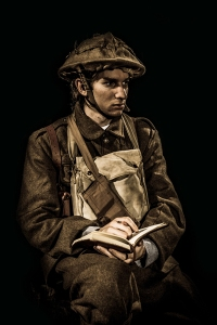 "Soldier/poet Tommy (Drew Benjamin Jones) writes down his thoughts and feelings to his wife in ""Truce: A Christmas Wish from the Great War"" at City Lights through Dec. 21st. (Photo by Mike Ko)"
